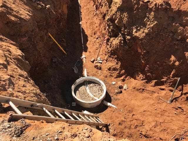 Sewage pipes in trench, with a starter manhole ring