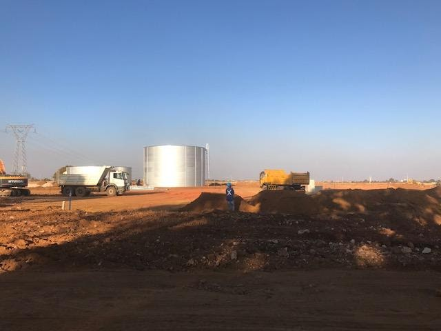Ground water tanks in Ext 7. Broken hard rock and road construction in the foreground.