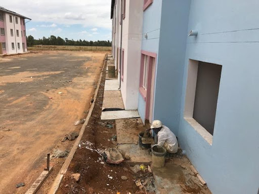 Cleaning and patching at the foot of the wall after apron was constructed