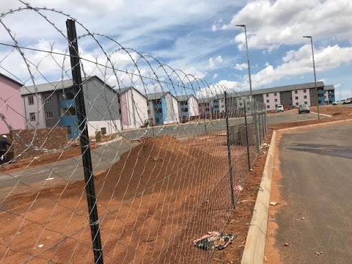 """First 5 blocks fenced off and topped with a razor wire to delineate from """"live"""" site sections"""
